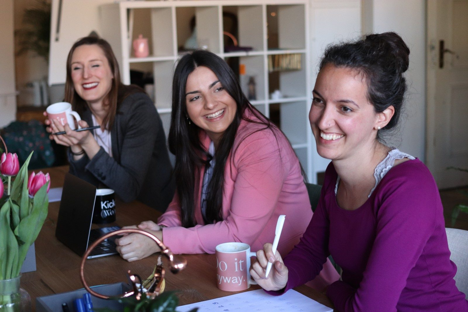 three women sitting by the table having coffee and smiling